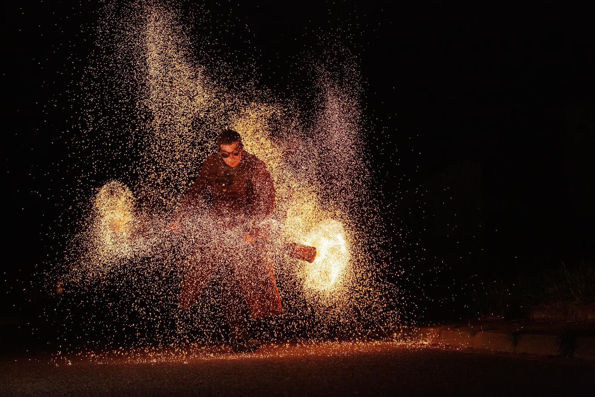 Feuerkünstler mit Funkenstab - Kohlestab bei einer Show